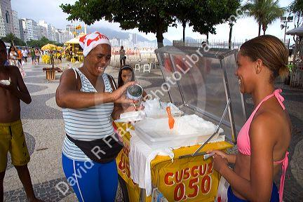 A street vendor selling cuscuz, a coconut snack, at the Copacabana Beach in Rio de Janiero, Brazil.