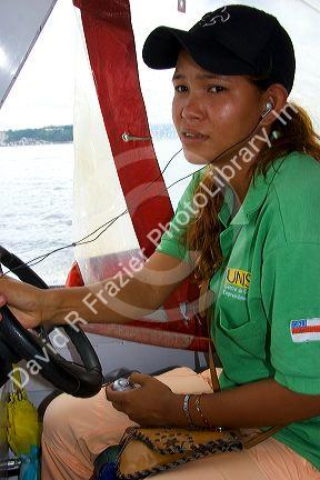 Brazilian woman listens to an MP3 player while driving an Amazon river boat at Manaus, Brazil.