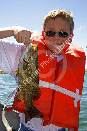A twelve year old boy wearing a life jacket and holding a for Bass fishing life jacket