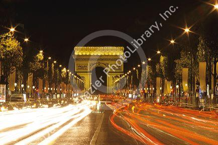 Traffic at night in the Champs Elysee in Paris, France with the Arc d'Triomphe.