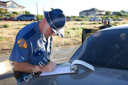 Police officer writing investigation report of a car