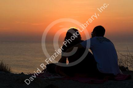 Couple watching the sunset over the Atlantic Ocean at Saint-Jean-de-Luz, Pyrenees Atlantiques, French Basque Country, Southwest France.