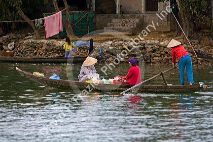 Vietnamese women travel by boat on the Perfume River at Hue, Vietnam.