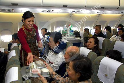 Vietnamese flight attendants serve food and drink to passengers on a Boeing airliner in Vietnam.