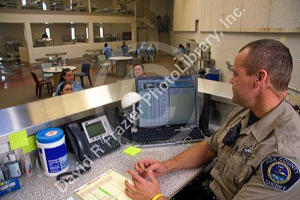 Security officer monitoring the female inmate dormatory of a county jail.