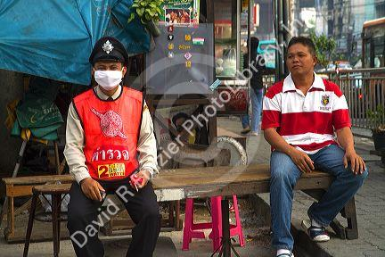 Thai police officer wearing a protective filtering mask to avoid