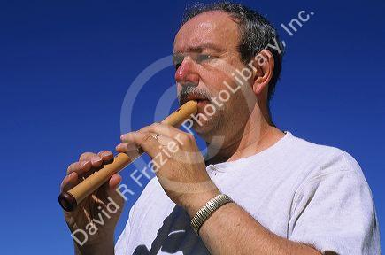 A man plays a soprano recorder.