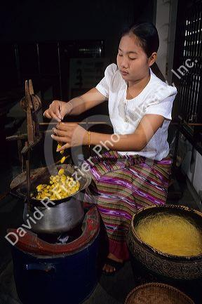 Thai woman spins silk from silkworm cacoons, Thailand.