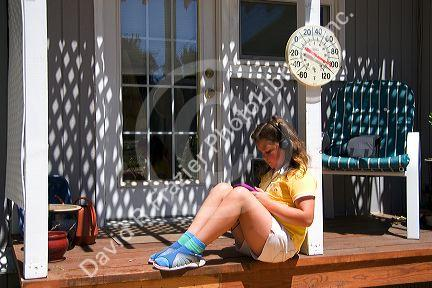 Nine year old girl listening to a walkman, personal cd player in 100 degree weather.
