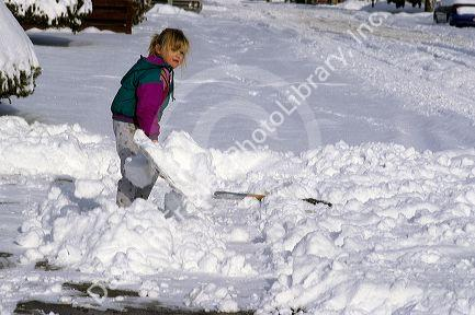 Young girl wearing winter coat shovels snow from the sidewalk.