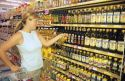 Woman shopping for olive oil in a grocery store.