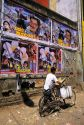 A man on bicycle and movie advertisements in Bangalore, India.
