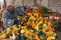 A mexican farm worker with harvested gourds at a farmers market in Fruitland, Idaho.