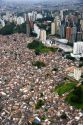 Aerial view of crowded favela housing contrasts with modern apartment buildings in Sao Paulo, Brazil.