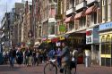 People walk and ride bicycles on the Damrak Strasse in Amsterdam, Netherlands.