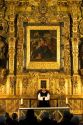A priest performing mass in front of a gold alter inside the Catedral Metropolitana located on the central square, the zocalo, Mexico.
