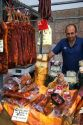 Vendor selling cured meats and cheese at an outdoor market in the town of Cangas de Onis, Asturias, northern Spain.