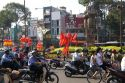 Vietnamese people ride motorbikes past Kentucky Fried Chicken sign and communist flags in Ho Chi Minh City, Vietnam.