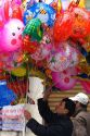 Street vendor selling colorful balloons for Tet in Hanoi, Vietnam.