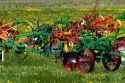 Colorfully painted antique plows on display at a farm near Corunna, Michigan, USA.