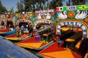 Colorful trajineras travel on the Xochimilco canals within Mexico City, Mexico.