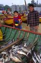 Fishermen sell fresh caught fish out of boats on the beach at Valparaiso, Chile.