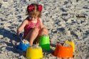 Three year old girl playing in the sand at a beach on the gulf coast of Florida, USA.